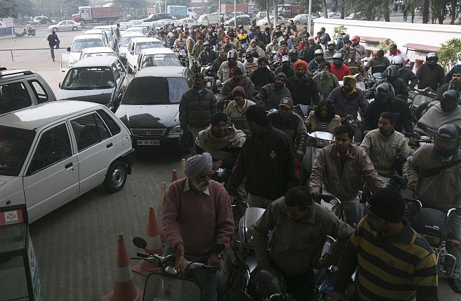 Motorists wait at a gas station to fill fuel in the northern Indian city of Chandigarh.