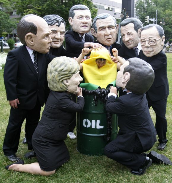 Activists from Oxfam, wearing masks depicting G8 leaders, place an activist dressed as a corn cob into an oil barrel in Sapporu.