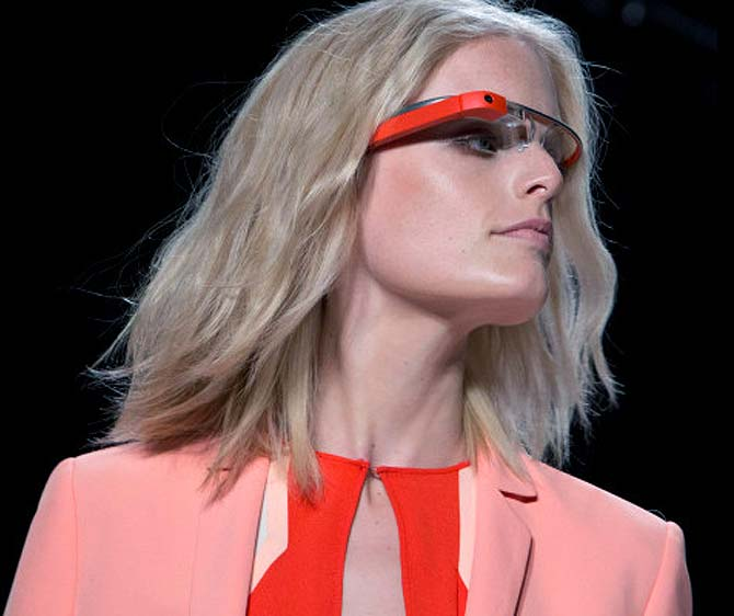A model wear rocks an orange pair of Google Glasses at the Diane von Furstenberg Spring/Summer 2013 runway show during New York Fashion Week.