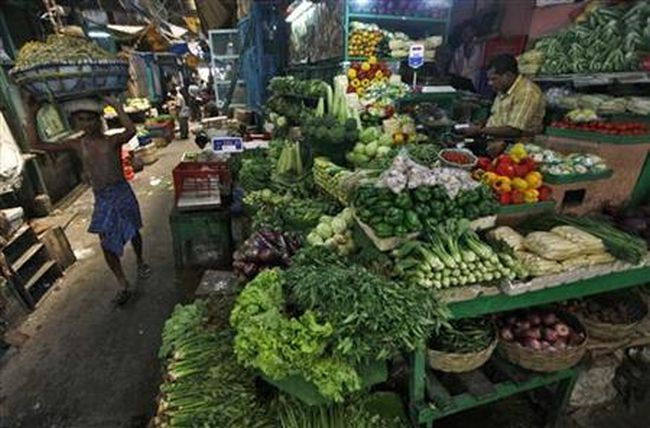 A labourer carries a packed basket of vegetables as a vendor waits for customers at his vegetables stall at a market in Kolkata May 14, 2012.