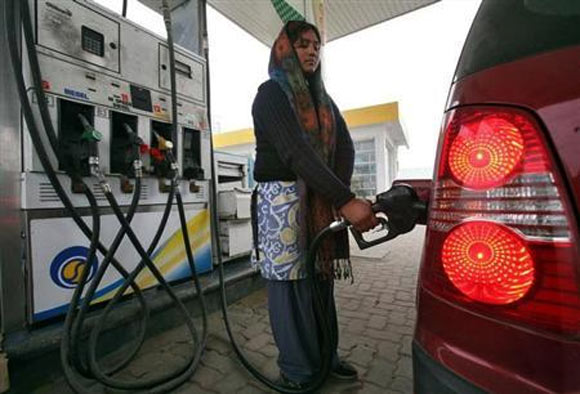 An employee fills a vehice with petrol at a fuel station in Jammu.