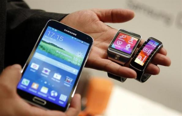 New Samsung Galaxy S5 smartphone (L), Gear 2 smartwatch (C) and Gear Fit fitness band are displayed at the Mobile World Congress in Barcelona February 23, 2014.