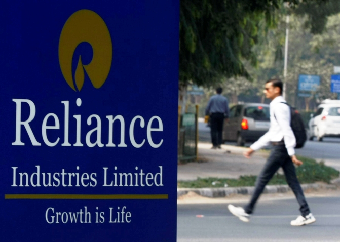A man walks past a Reliance Industries Limited sign board installed on a road divider in Gandhinagar.