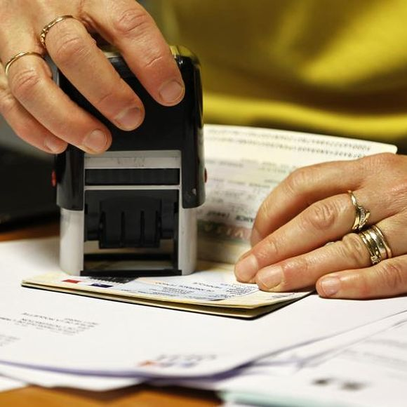 An immigration officer stamping a visa.
