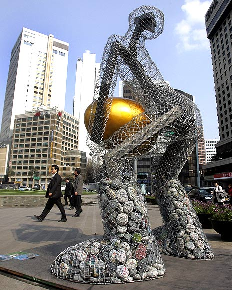 People walk past a statue titled 'Seoul broods a golden egg' at the Seoul city hall plaza in central Seoul.