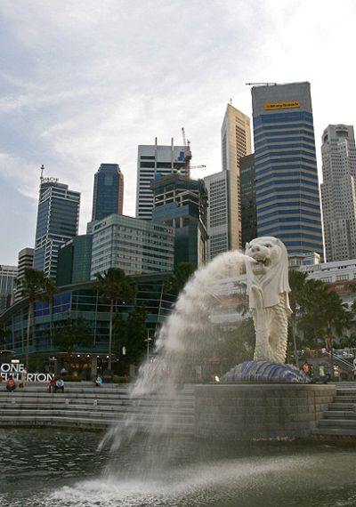 People sit on the steps near the Merlion, in Singapore's financial district June 10, 2009. Singapore's economy is expected to shrink at a slower pace in the rest of 2009 after a record annual contraction in the first three months of this year as analysts believe the worst might be over.