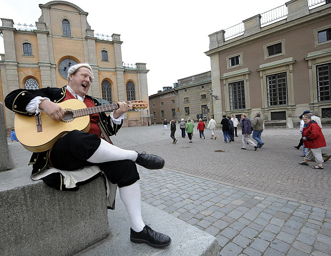 Tour guide Henrik Miko, dressed like the Swedish 18th century poet and composer Carl Michael Bellman, sings and plays his guitar in front of the Stockholm cathedral.