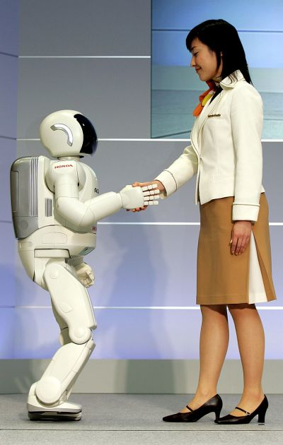 Honda Motor's humanoid robot,next-generation ASIMO steps in the direction being pushed by a model at Honda's office in Wako.