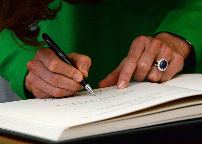 Catherine, Duchess of Cambridge, signs a visitors' book.