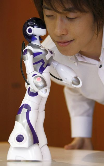 Sega Toy's female humanoid robot, Eternal Maiden Actualisation (E.M.A), kisses a man at its demonstration in Tokyo.