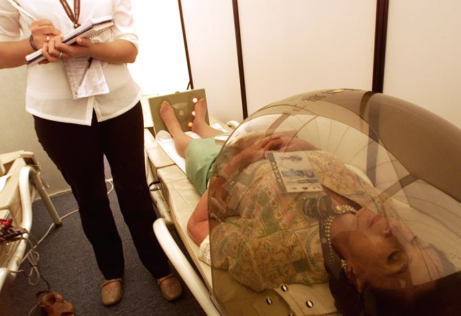 A therapist checks on her patient as she undergoes stress relieving procedure.