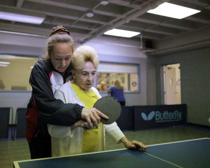 Holocaust survivor Betty Stein, 92, (R) is helped by coach Irina Jestkova as she plays ping pong at a program for people with Alzheimer's and dementia at the Arthur Gilbert table tennis center in Los Angeles, California.