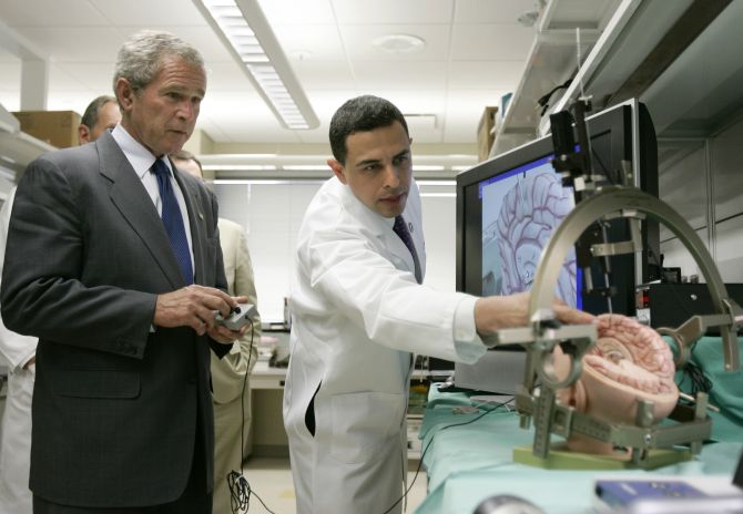 U.S. President George W. Bush (L) uses a remote control to deliver a simulated pacemaker to a part of a mockup human brain, as Ali Rezai, director of the center for advanced study of therapies for brain injury guides him, at the Cleveland Clinic in Ohio.