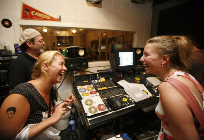 Elvis fans Ilja Klink (L) and Eva Niermeyer of the Netherlands laugh at a recording of their singing with Elvis at Sun Studios in Memphis, Tennessee.