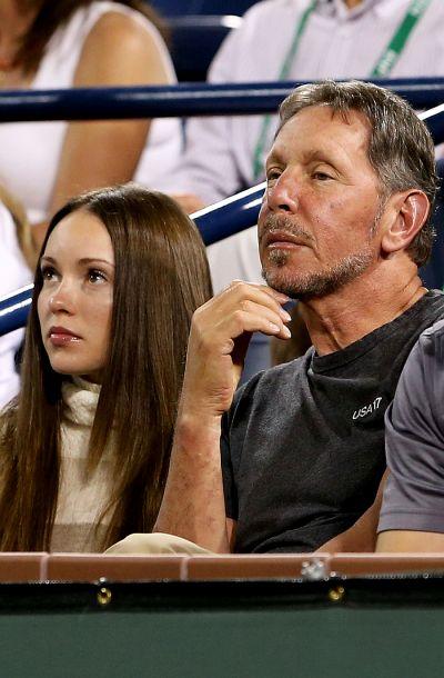 Nikita Kahn and Larry Ellison watch Roger Federer play Rafael Nadal.