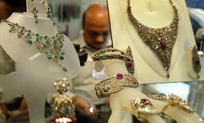 A shopkeeper arranges diamond jewellery in his stall at the India International Jewellery show, in Bombay.
