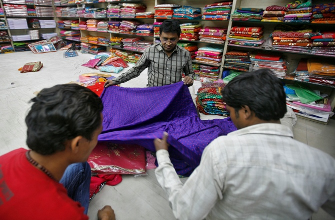 A shopkeeper displays a saree.