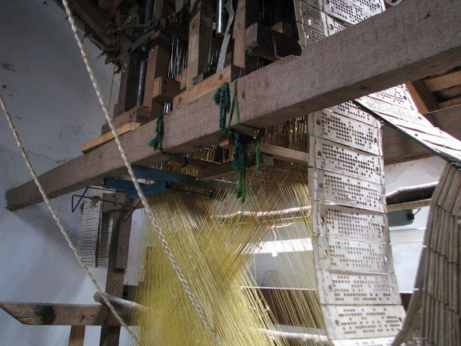 The complicated yet elegant pattern and string pulling system of a hand-loom to make fine silk saris.