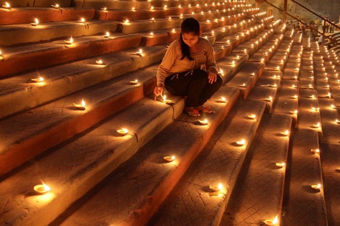 A Hindu devotee lights an earthen lamp on the steps of Sindhiya Ghat during the Karthik Purnima and Dev Diwali festival in Varanasi.