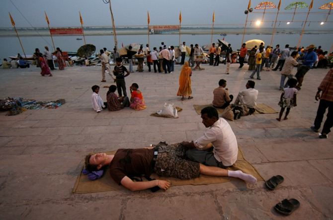 An Indian masseur gives a massage to a tourist on the banks of river Ganges in Varanasi.