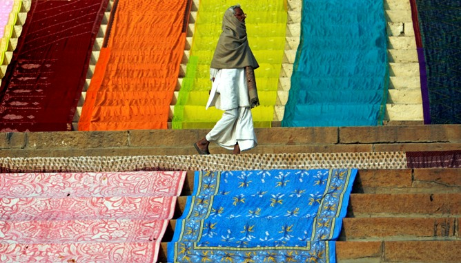A man walks past Saris placed on the ground for drying by washermen on the banks of river Ganges in Varanasi.