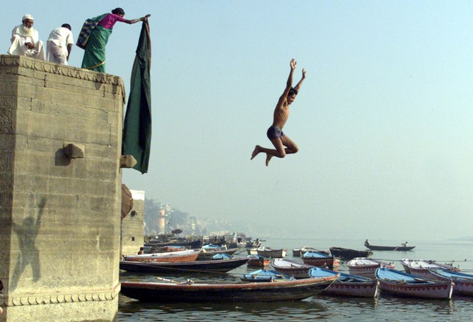 An Indian youth jumps into the water on the banks of Ganges in Varanasi.