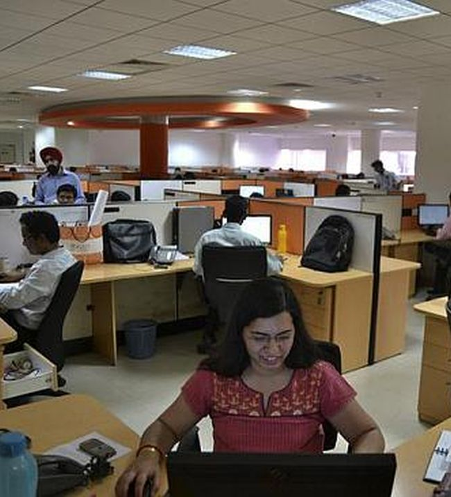 Employees work at the headquarters of iGate in Bangalore.