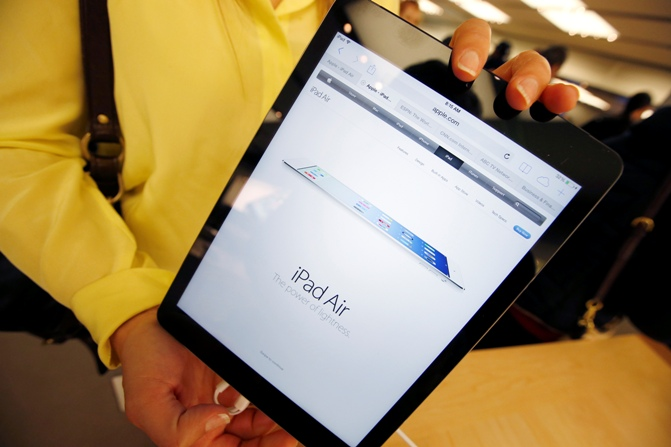 A customer holds a new Apple iPad Air tablet inside the Apple Store on New York's fifth avenue, after the new iPad went on sale.