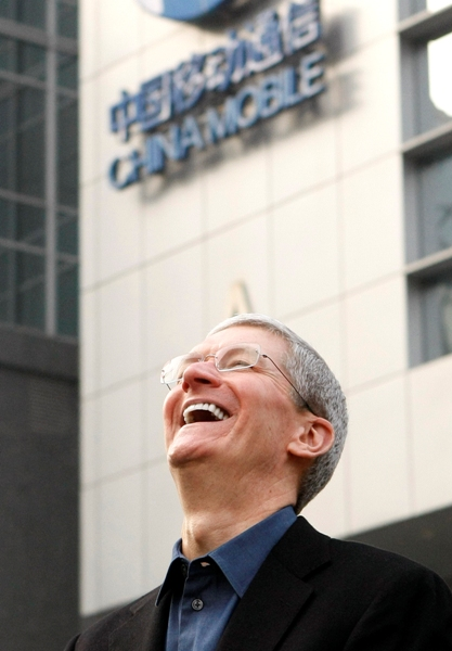 Apple Inc. CEO Tim Cook laughs outside a China Mobile store in Beijing.