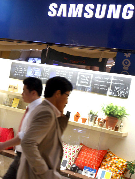People walk at a Samsung Electronics store in the Gangnam area in Seoul.