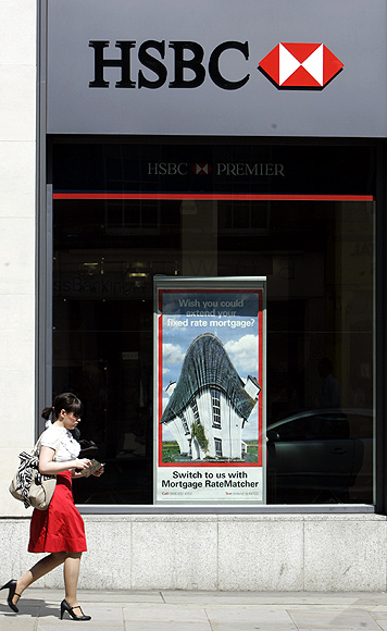 A pedestrian passes a branch of HSBC in London.