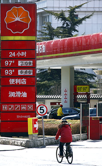 A woman rides her bicycle past a PetroChina petrol station in central Beijing.