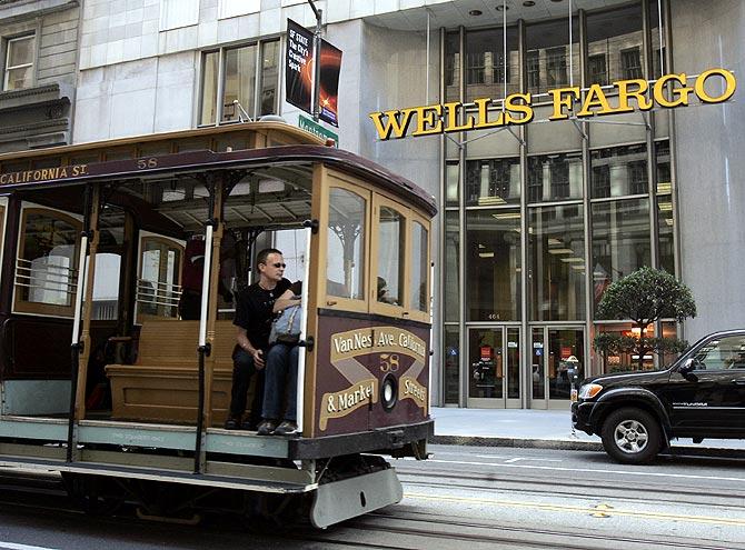 A cable car passes a Wells Fargo bank building along California Street in San Francisco.