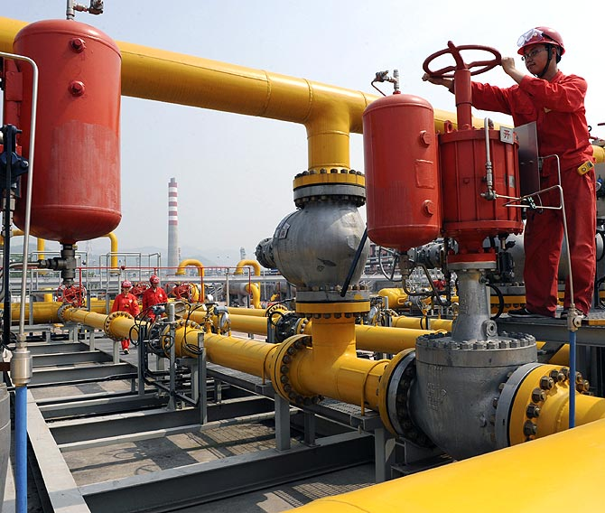 An employee checks on Sinopec natural gas transmission facilities in Xuanhan county, Sichuan province.