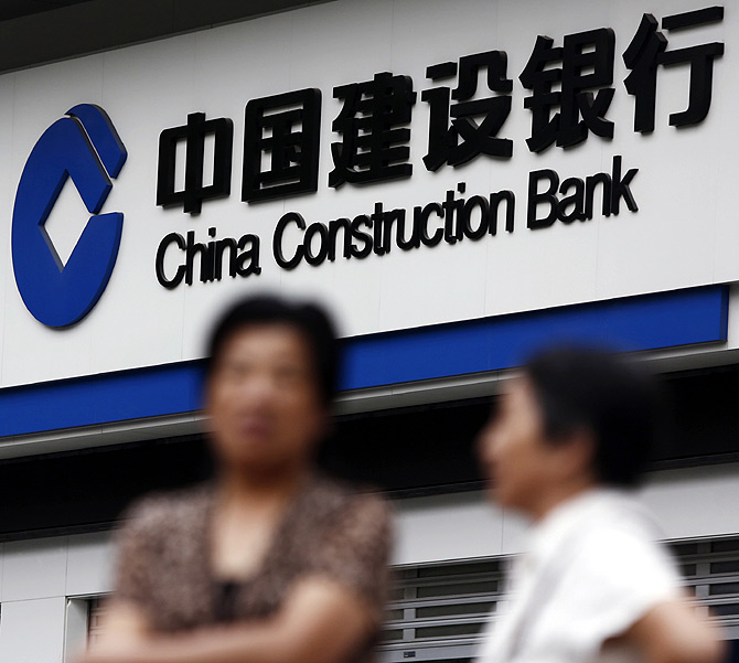 Residents stand outside a branch of the China Construction Bank (CCB) in Shanghai.