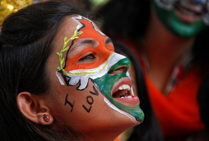 A girl, with her face painted in the colours of India's national flag, chants slogans as she takes part in a cultural program to celebrate India's Independence Day in Chandig