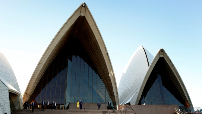 Britain's Prince William and his wife Catherine, Duchess of Cambridge, walk together from the top of the steps as they leave Sydney Opera House.