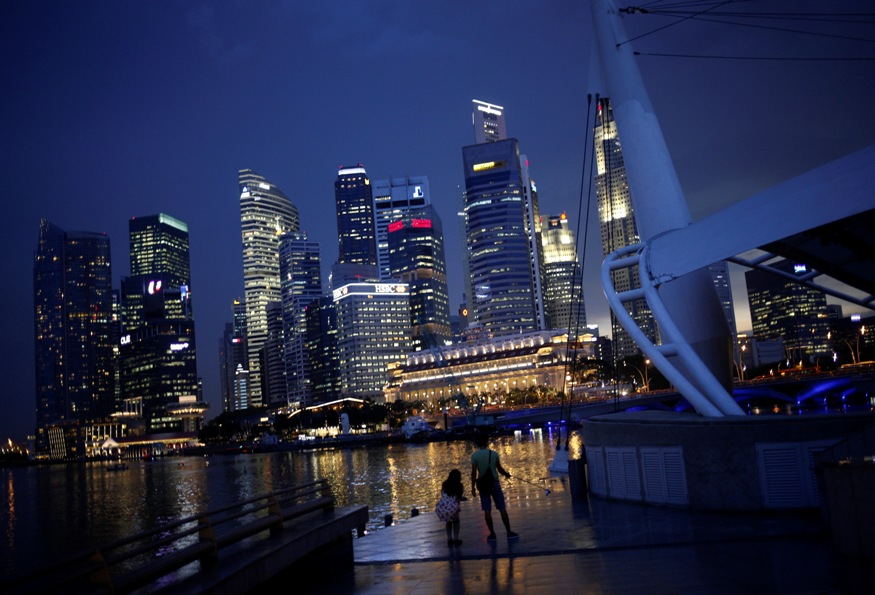 People take photos with the skyline of the financial district of Singapore in the background.