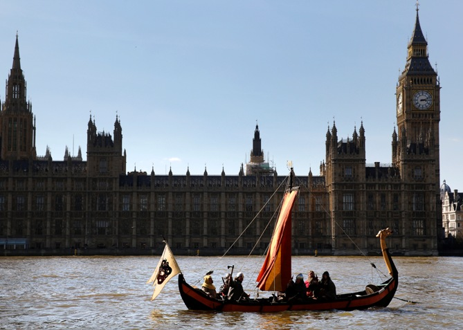 Members of a re-enactment group dressed as Vikings sail a replica Viking Longboat past the Houses of Parliament in London.