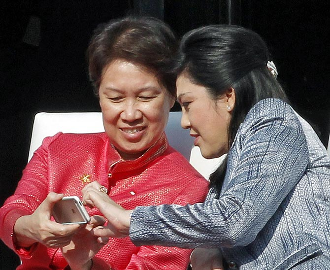Thailand's Prime Minister Yingluck Shinawatra (R) and Ho Ching, wife of Singapore's Prime Minister Lee Hsien Loong, look at a mobile phone during the ceremonial flag down of ASEAN-India car rally.