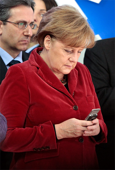 German Chancellor Angela Merkel checking her mobile phone.