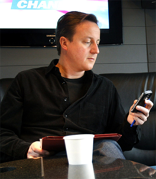Britain's Prime Minister David Cameron looks at his mobile phone on his bus during an election campaign trip in London.