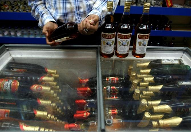 A man checks an alcohol bottle inside a wine shop in Siliguri.
