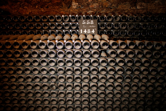 Billecart-Salmon Champagne bottles are stacked in a cellar.