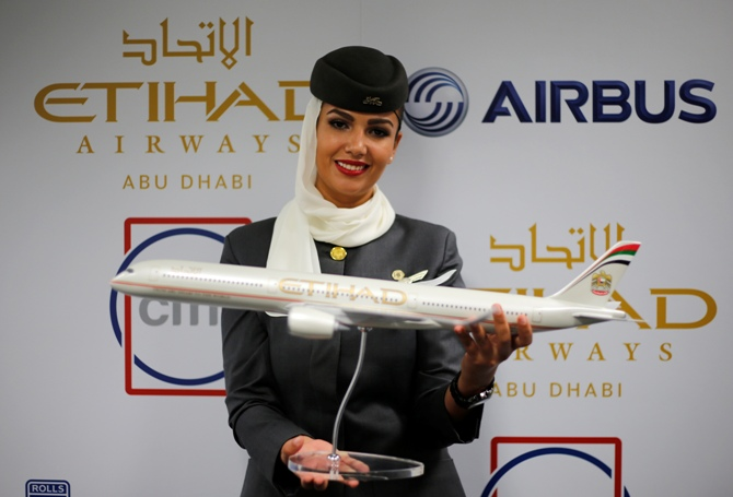 A flight attendant of Etihad Airways holds a model of the Airbus A350 during the Dubai Airshow.