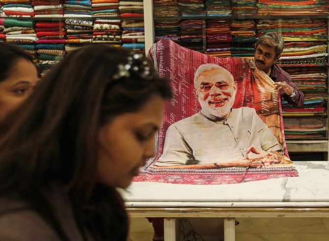 A salesman shows a sari, a traditional women's clothing, printed with a portrait of Hindu nationalist Narendra Modi, the prime ministerial candidate for India's main opposition Bharatiya Janata Party.
