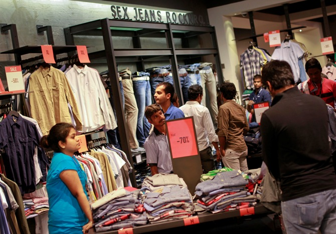 People shop for clothes at a store during a seasonal sale inside a shopping mall.