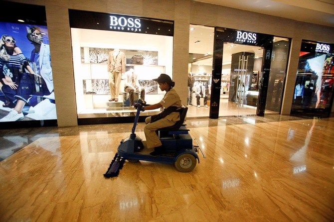An employee operates a floor cleaning machine in front of a Hugo Boss showroom inside a shopping mall.