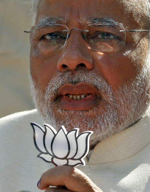 Hindu nationalist Narendra Modi, the prime ministerial candidate for India's main opposition Bharatiya Janata Party (BJP), holds a lotus cut-out after casting his vote.