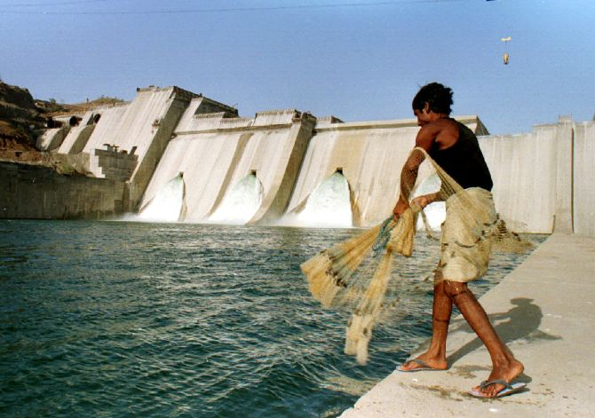A fisherman casts his net in the waters in front of the half- completed Sardar Sarovar dam on the Narmada river.